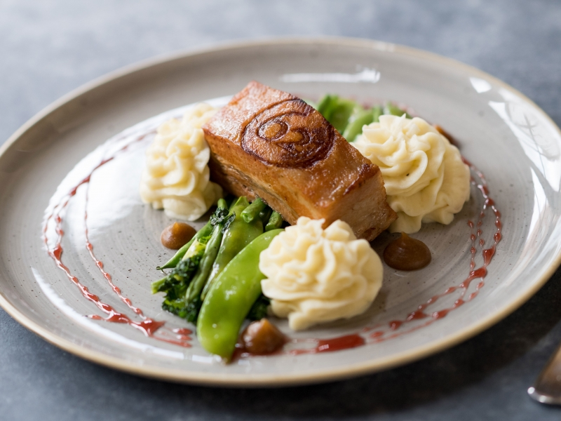SLOW ROASTED PORK BELLY,Creamy mash potato, buttered greens, burnt apple purée & a port reduction